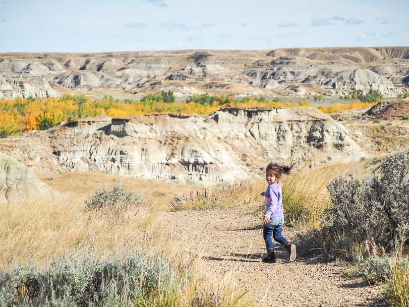 A girl running in the badlands of Dinosaur Park