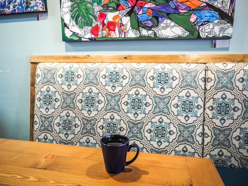 Coffee on a table and artwork on the wall at Penny Coffee House, one of the best cafes in Lethbridge