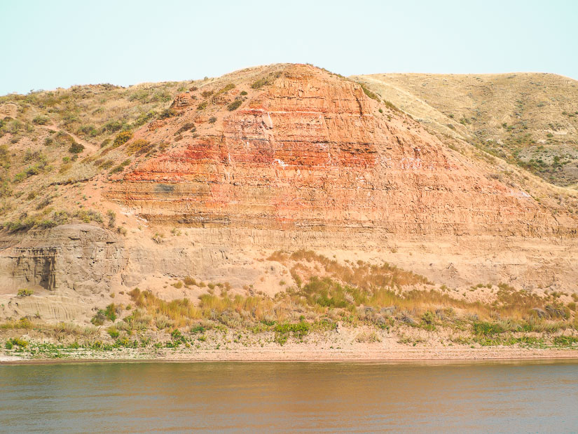 Red cliff towering above a river at Echo Dale Regional Park
