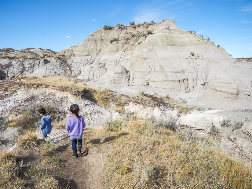 Badlands scenery and two kids walking on the Trail of the Fossil Hunters, Dinosaur Park