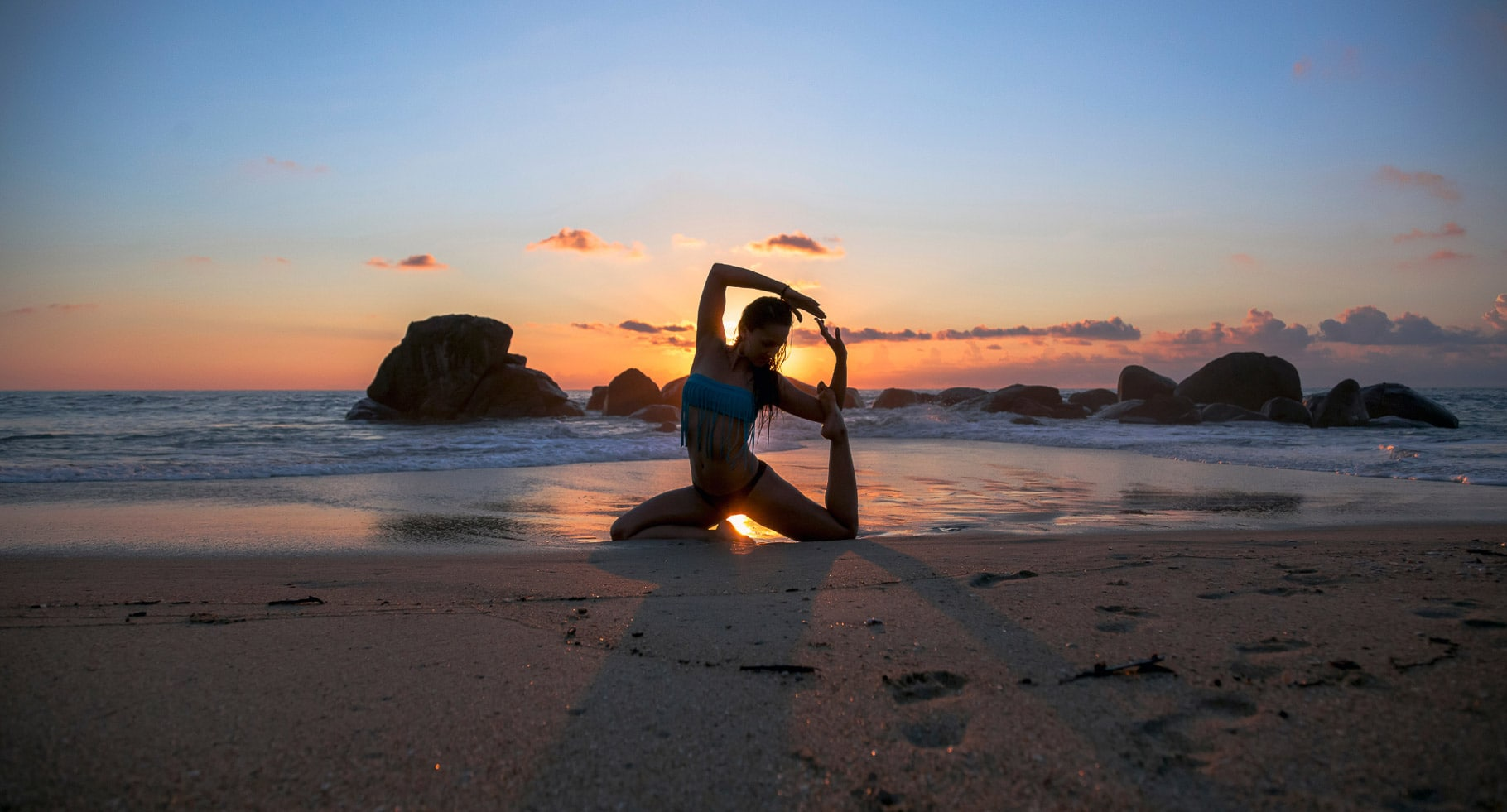 A sunset and woman on a beach doing yoga while traveling