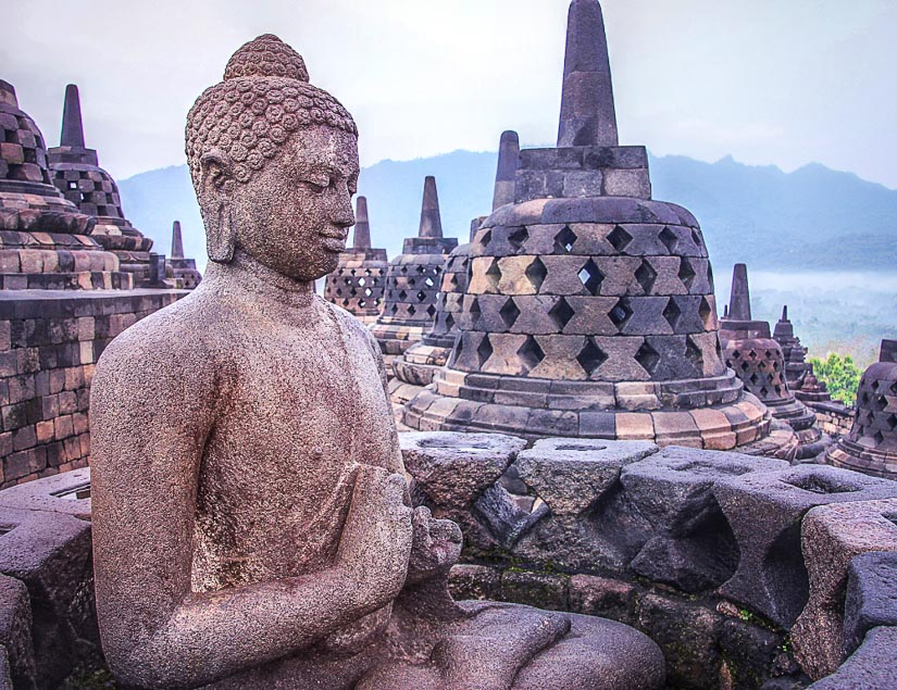 Buddha statue at the top of Borobodur, one of the most fascinating temples in Southeast Asia