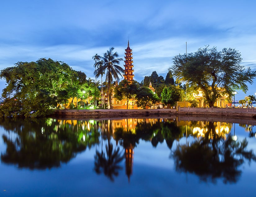 View of Tran Quoc Pagoda reflecting in the lake in the early evening, Hanoi, Vietnam