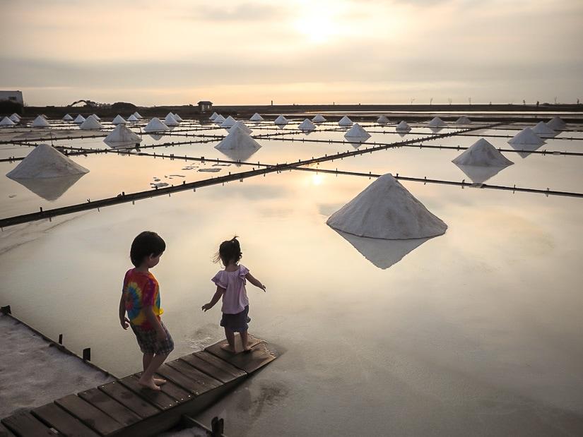 Two kids standing beside the salt fields in Tainan Taiwan