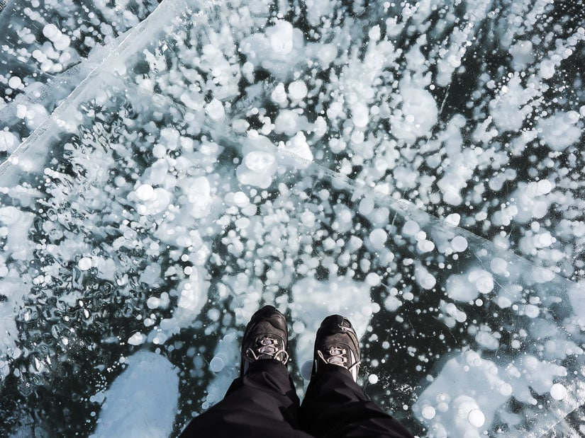 Feet standing on ice bubbles at Abraham Lake