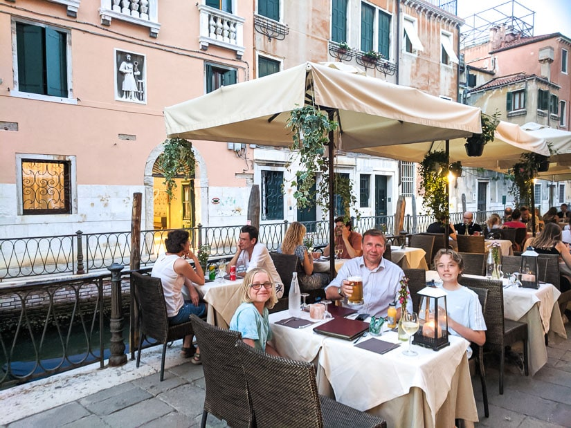 A family of travelers having a meal beside a canal in Venice