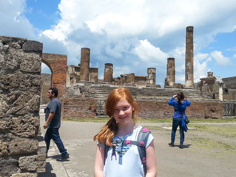 A child posing in front of the ruins of Pompeii in Italy