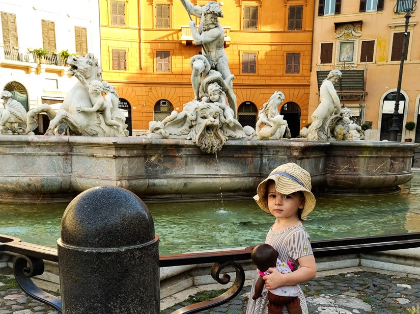 A toddler in front of a famous fountain in Rome