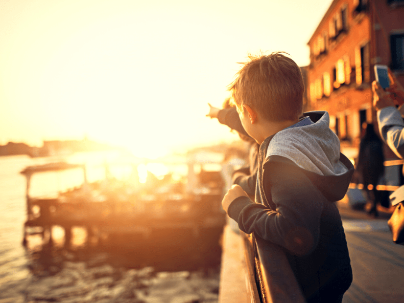 A kid looking over a canal in Venice at sunset