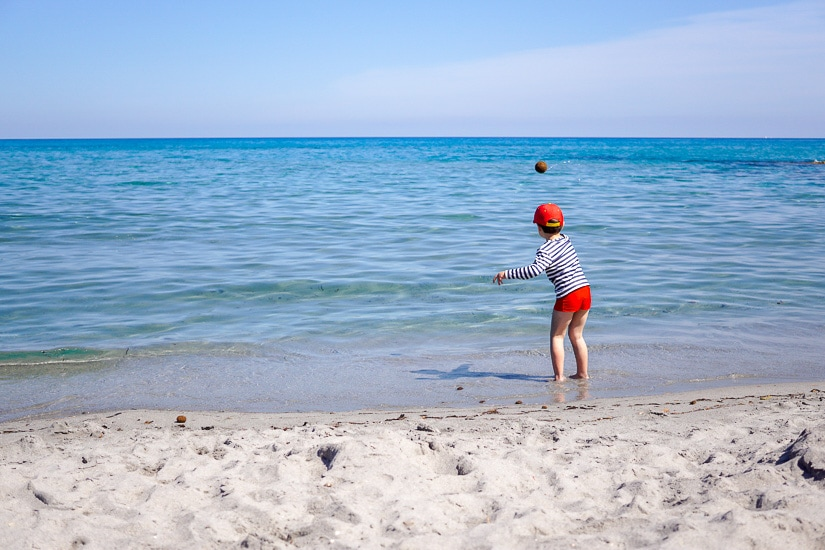 A kid playing on the beach in Sardinia