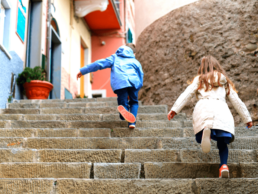 Some kids runnign up a staircase in Cinque Terre