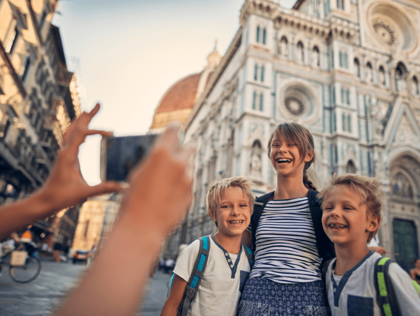 Some kids posing for a picture in Florence with ancient architecture behind them