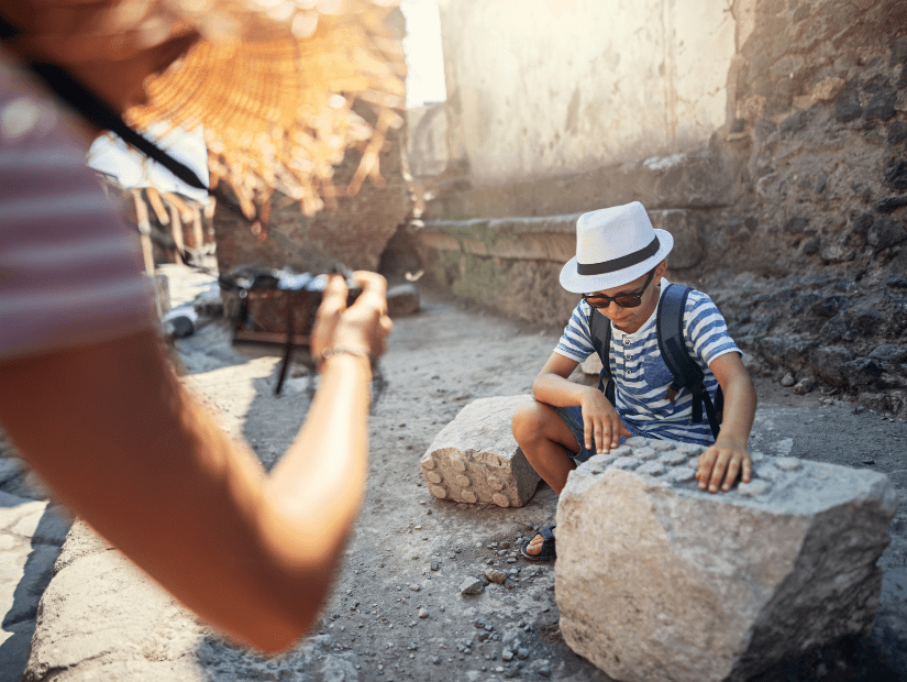 A parent taking a picture of a kid who is playing amongst the ruins of Pompeii