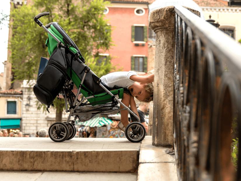 A kid in a stroller on a bridge in Venice, Italy