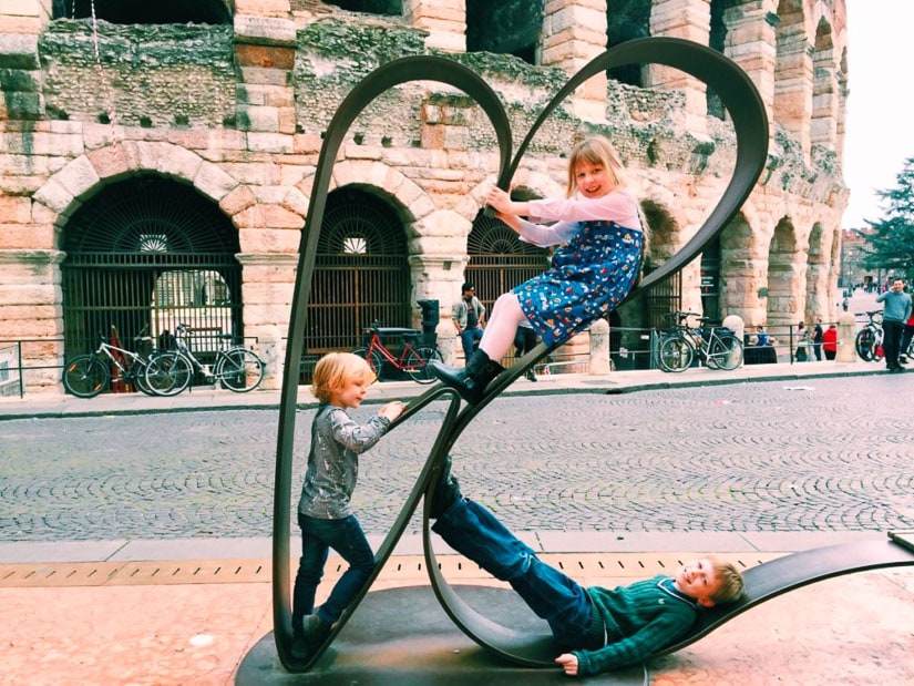 Some kid travelers playing on the streets in Verona Italy