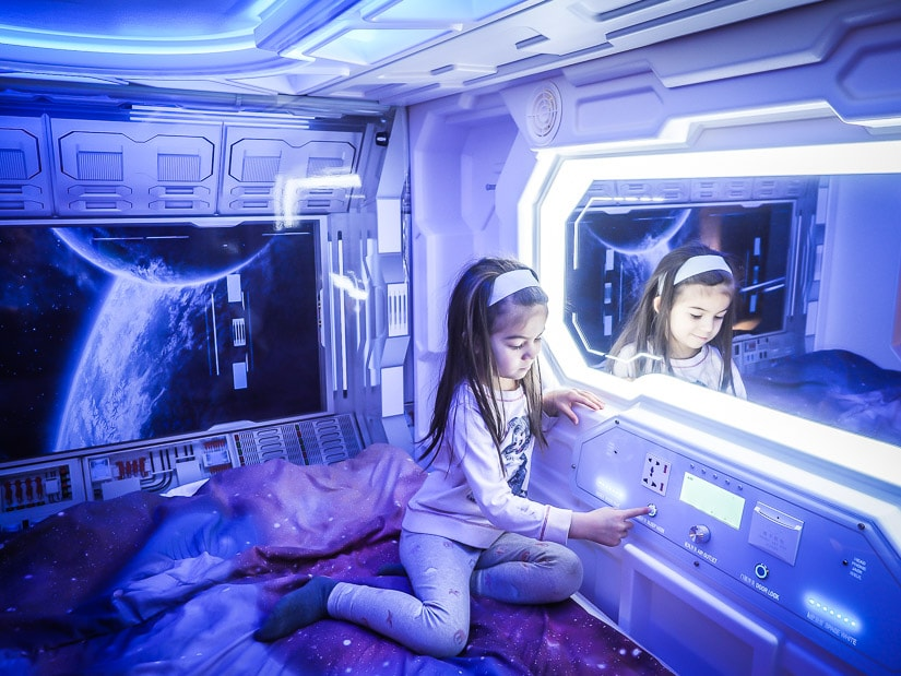 A girl inside a space pod-themed bed in Fantasyland Hotel, West Edmonton Mall