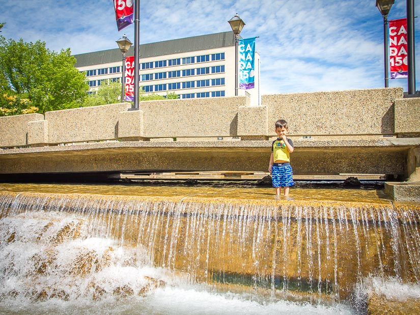A boy playing in a water fountain at the Legislature Grounds in Edmonton
