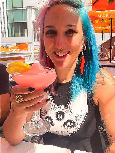 A woman with colorful hair having a cocktail on the patio at Central Social Hall in Edmonton
