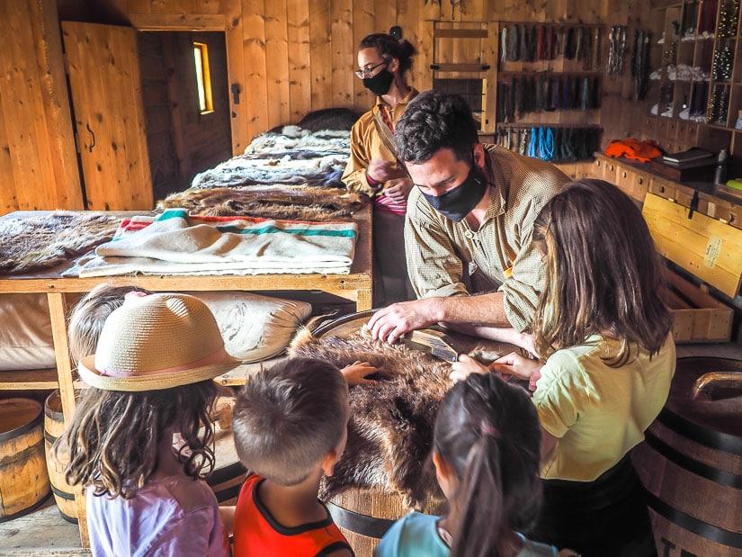 An interpreter showing some furs to kids at Fort Edmonton Park