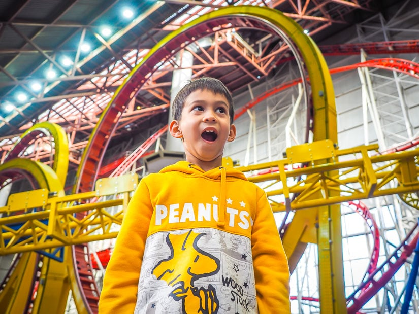 A boy looking excited as he stands in front of a huge indoor rollercoaster in Galaxyland, West Edmonton Mall