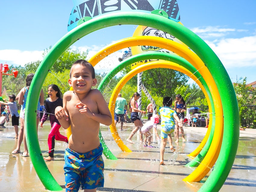 A boy running through a row of sprinklers at Jackie Parker Spray Park in Edmonton