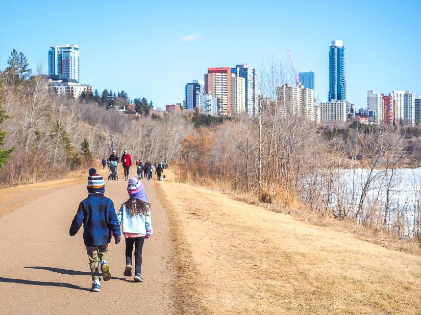 Two kids walking along a path beside the river in Edmonton