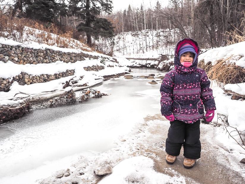 A girl standing beside a frozen creek in Mill Creek Ravine